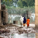 Victims of floods in Pakistan walk through water-filled streets in Nowshera. UN Photo/WFP/Amjad Jamal.