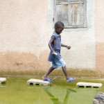 A child steps over stones to avoid flooded streets just outside of Dakar, Senegal. International Federation of Red Cross and Red Crescent Societies/Ricci Shryock.